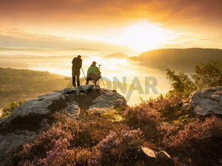 Pair of landscape photographers standing on cliff, taking photos  of misty landscape