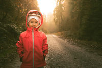 Child standing on wet path in moody forest.