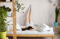 Young slim brunette woman in casual clothes lying down on wooden bed with legs raised up on wall at home