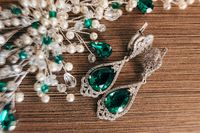 Earrings with a large emerald and an ornament of white beads on a brown background with a rough texture.