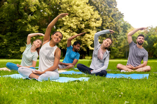 group of people exercising at summer park