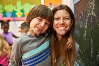 Glücklicher Junge mit Lehrerin oder Tagesmutter
