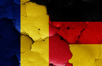 flags of Romania and Germany painted on cracked wall
