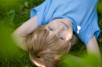 little boy in bkue t-shirt lying on the grass