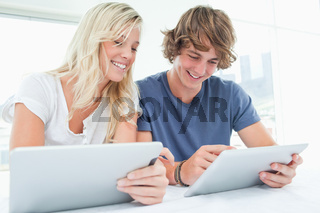 A man and woman both using their tablets