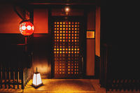 Traditional wooden door entrance with illuminated laterns in the old town Gion district in Kyoto, Japan