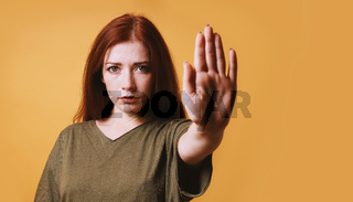 serious young woman making stop gesture with left hand