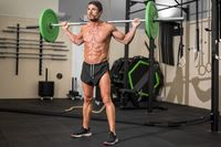 Fit man bodybuilder doing barbell squats at gym.