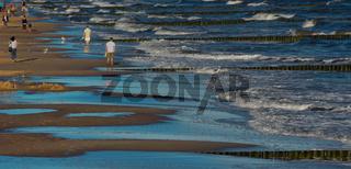 Menschen spazieren am Abend am Meer
