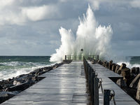 Lighthouse on the pier of Norre Vorupor during storm and heavy sea, Jutland, Denmark