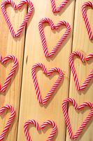Composition of multiple candy canes in shape of heart on wooden background