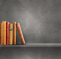 Row of old books on grey shelf. Square background