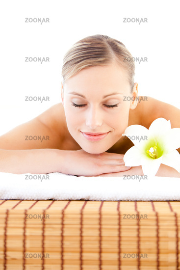 Close-up of a delighted woman lying on a massage table with a flower in a health spa