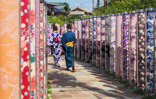 Couple in traditional clothing walking through Kimono forest with poles decorated with Japanese fabrics at Arashiyama Station in Kyoto, Japan