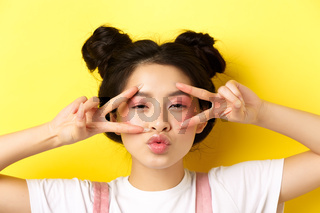 Carefree asian girl showing v-signs and kissing lips, standing on yellow background