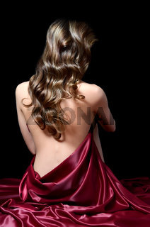 The beautiful woman with long hair in a red silk