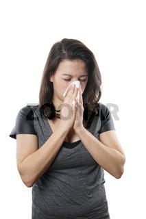 junge Frau putzt sich die Nase