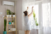 Young girl in casual clothes standing facing window and straightening curtain