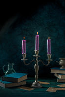 Candle magic. Purple candles and occult books