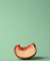 A piece of a flat peach on a green background