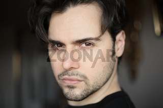 Close-up portrait of a handsome young spanish guy. Bearded face.