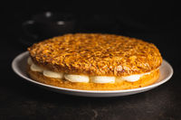 Sweet almond cake. Pie with cream and almonds on black table.
