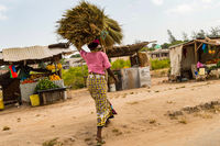 African woman carrying a bundle on her head in a small market near Watamu in Kenya