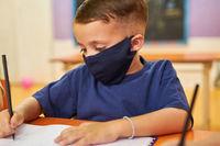 Junge mit Schutzmaske wegen Covid-19 und Coronavirus