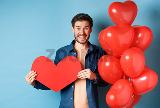 Valentines day concept. Smiling man say I love you, holding paper red heart cutout, standing near romantic balloons, blue background