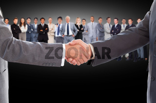 Businessmen shaking hands with large team behind them
