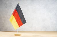 Germany table flag on white textured wall. Copy space for text, designs or drawings