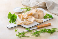 Organic oyster mushrooms with herbs and salt on cutting board