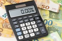 calculator showing zero percent interest rate on Euro banknotes