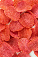 Red chips with hot pepper taste on a white background. Beer snack. Close-up.