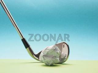 Golf club with a crumpled paper ball as golf ball