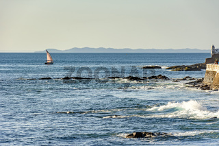 Rudimentary fishing boat sailing on the horizon during sunset in All Saints Bay in the city of Salvador