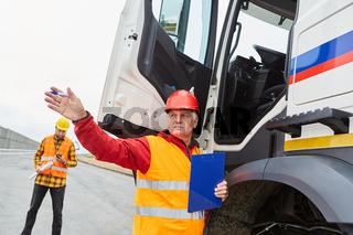 Bauleiter an LKW mit Checkliste gibt Richtung vor