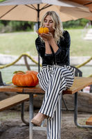 A Lovely Blonde Model Poses In A Pumpkin Field During The Halloween Holiday