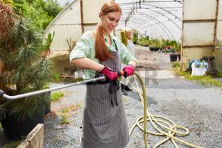 Gärtner Lehrling befestigt Schlauch an der Brause