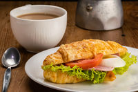 Ham cheese croissants and a cup of milk coffee for breakfast.