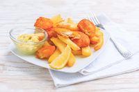 Fish and chips with dip and lemon on white plate