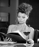 Beautiful girl reading menu in restaurant. Black a