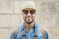 Close up shot of handsome man traveler having nice walk in old town during summer vacations. Man wearing stylish mirrored lens sunglasses and hat standing in urban setting.