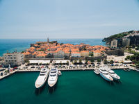 Huge expensive yachts moored on the pier near the old town of Budva, Montenegro. Aerial photo from the drone.