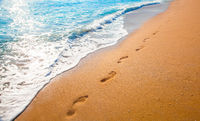 footprints on  tropical beach and beautiful  wave