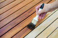 hand holding a brush applying varnish paint on a wooden garden table - painting and caring for wood with oil