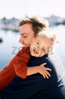 Father and daughter are hugging during their walk by the sea