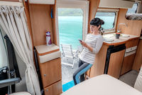Woman in the interior of a camper RV motorhome with a mobile phone in hand