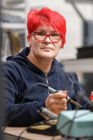 Industrial worker woman soldering cables of manufacturing equipment in a factory