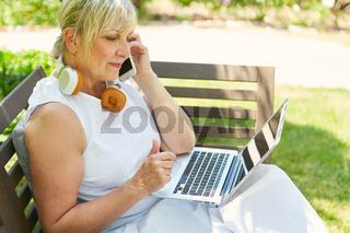 Frau im Garten am Laptop telefoniert mit Smartphone